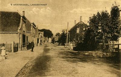 De Langestraat met rechts de toegangspoort, met petroleumlamp, naar het schoolplein omstreeks 1915.