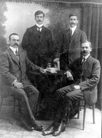 Vier mannen met snorren, twee zttend twee staand. Herkent u de foto?
