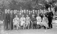 Groepsfoto rij mannen staand, rij vrouwen zittend. Herkent u deze foto?