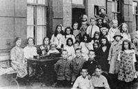 Groepsfoto met kinderen bij gebouw, herkent u deze foto?