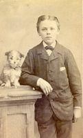 Staande jongen leunend op kastje met hondje, herkent u deze foto?